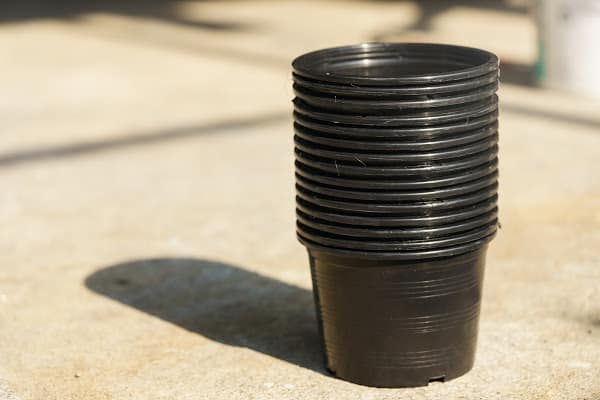 black plastic pots stacked on top of one another